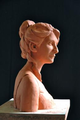 Terra cotta bust of woman with hair in pony tail against black background