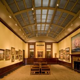 Formal art gallery with framed paintings hanging on the walls under a frosted glass ceiling