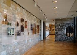 History exhibit with glass panels mounted on a stone wall